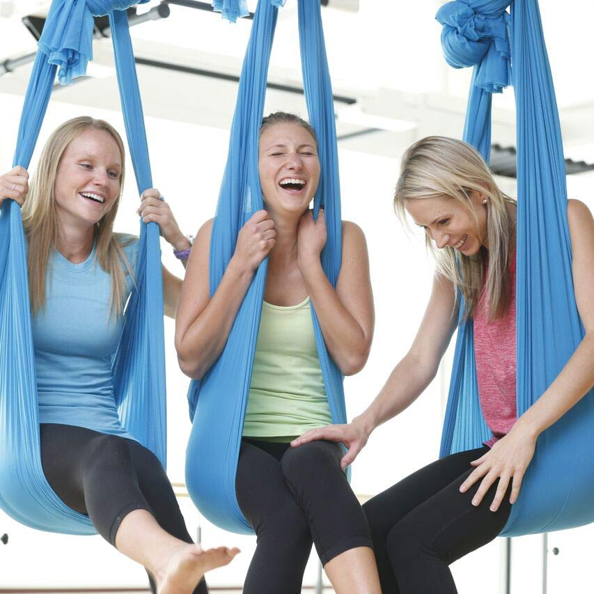 Three women laughing in aerial yoga hammocks at a certifed AIReal Yoga studio Spa Anjali in Avon, Colorado.