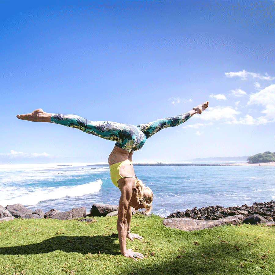 Carmen Curtis, the founder of AIReal Yoga, doing a handstand at Wanderlust Festival Hawaii.